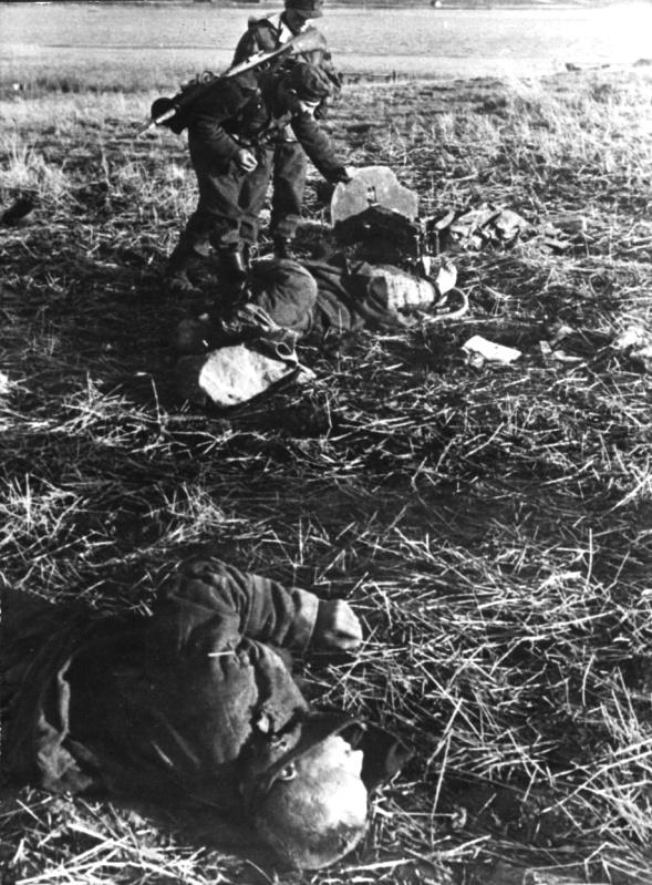 2 нем. солдата осматривают пулемет «Максим» у тел погибшего расчета. 43.jpg