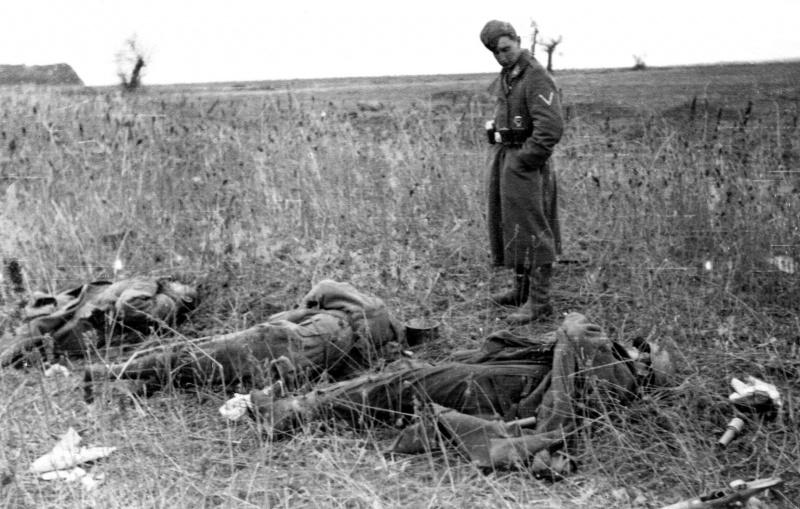 Немецкий солдат рядом с погибшими красноармейцами.jpg