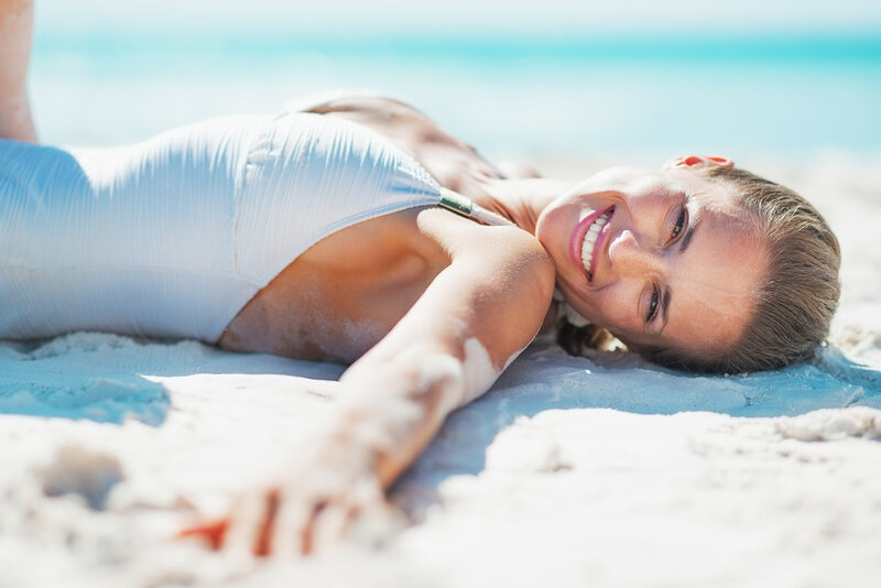 Portrait of smiling young woman in swimsuit sunbathing on beach