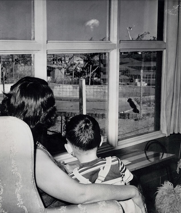 Safe in the living room of her Las Vegas, Nevada, home, Mrs. Jacqueline Buck and her son watch the mushrooming cloud from an atomic test blast some 75 miles away