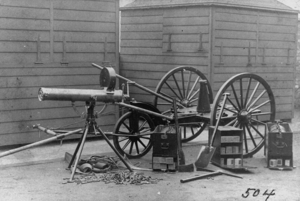 Gatling machine gun. On a tripod mounting, with transporting three-wheel limber and boxes of ammunition and other supporting gear behind. Photo received by the Bureau of Ordnance, 1885