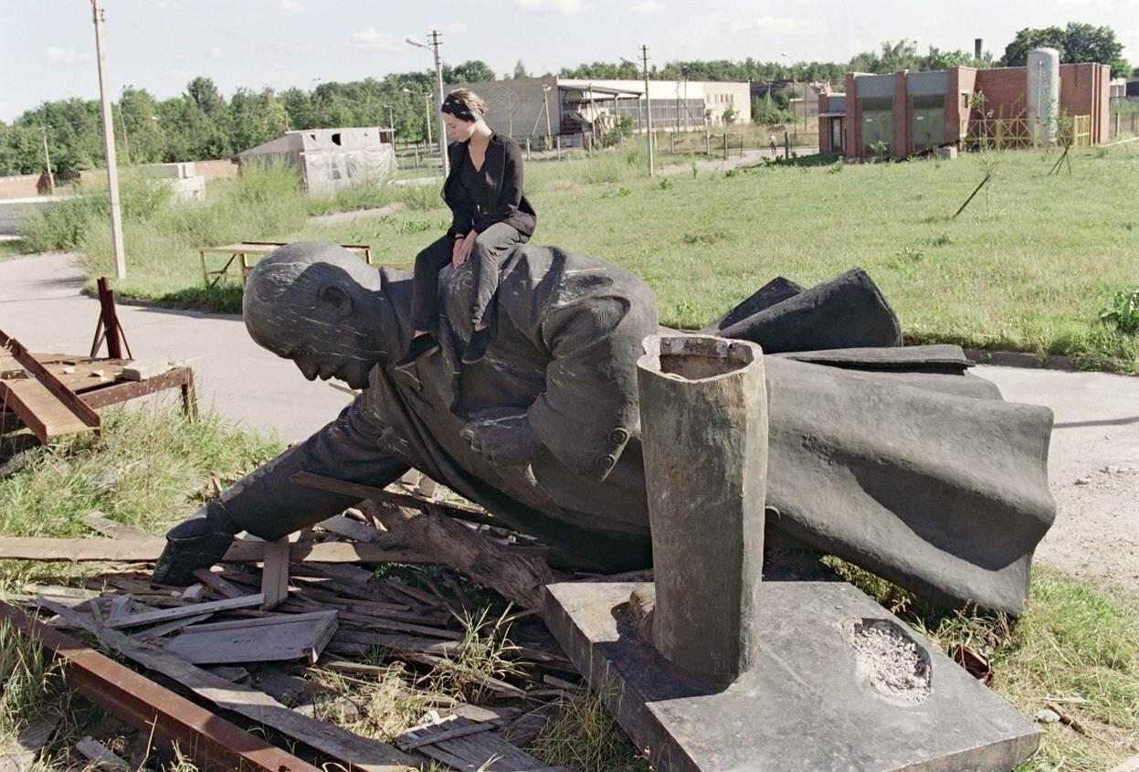 Молодая девушка сидит на сброшенной статуе Ленина в Вильнюсе