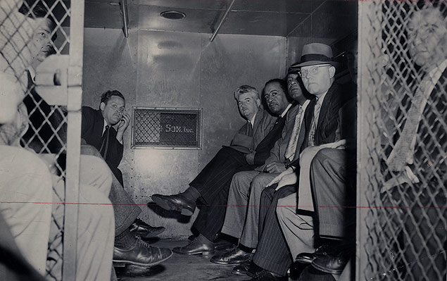 Eleven convicted Communists pictured in a prison van en route to federal court for their sentencing.jpg