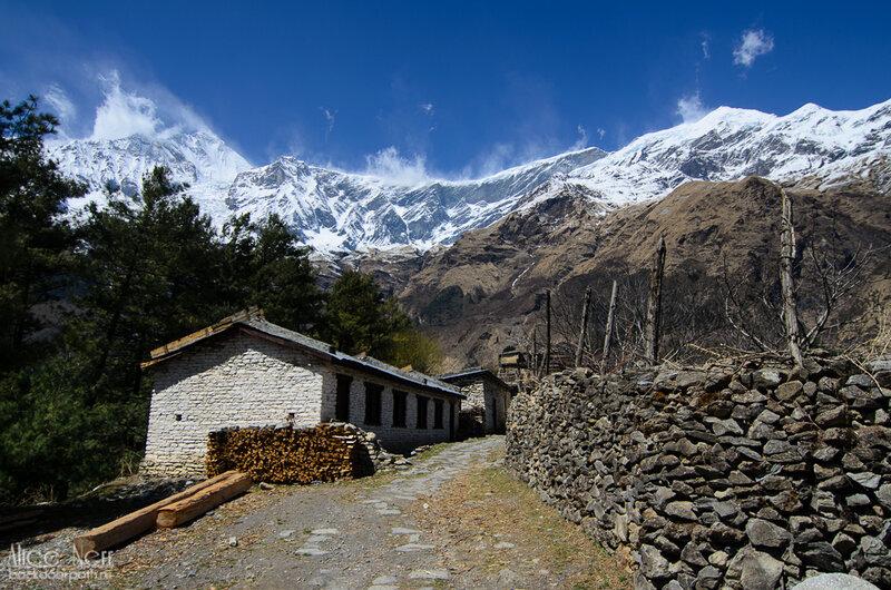 идем через непальскую деревеньку к водопаду близ кобанга в гималаях, непал