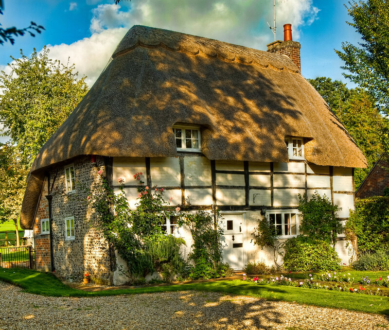 Dappled sunlight on a pretty thatched cottage at Stoke in Hampsh