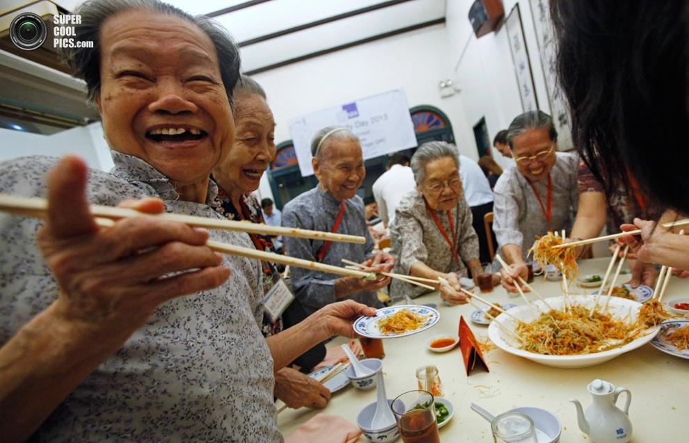 Пожилые женщины едят традиционный новогодний салатюй-шэн в ресторанекитайскогоквартала, Синга