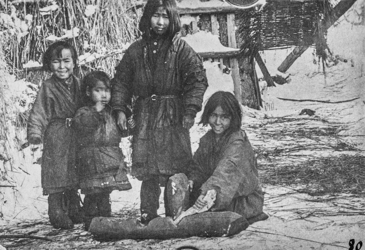 Четыре девушки айнов, одна из них разминает кожу