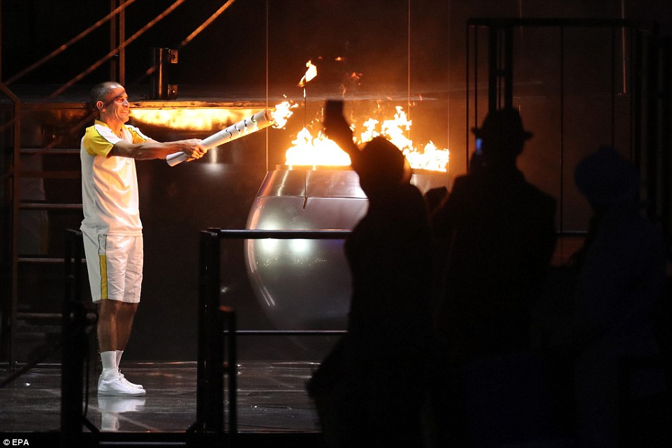 Бразильский марафонец Вандерлей Кордейру ди Лима зажигает олимпийский огонь.