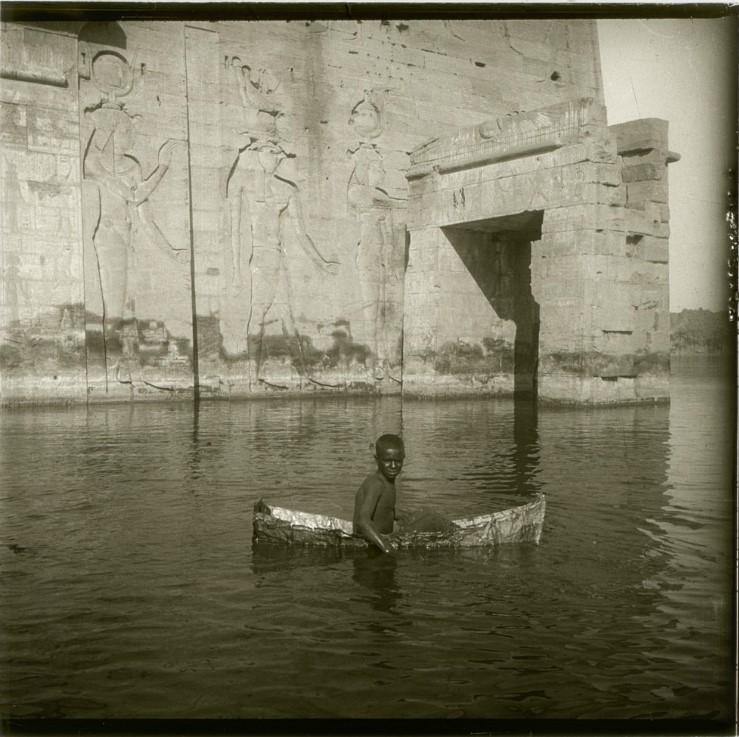 1910. Сей маленький спортсмен (по происхождению Бешари) ради бакшиша постоянно плавает в своей жестяной скорлупе. ежеминутно вычерпывая ковшом воду. Египет, остров Филе