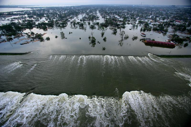 24. Вода льется через прорыв в дамбе, разрушения в котором были вызваны сильными ветрами и паводком.