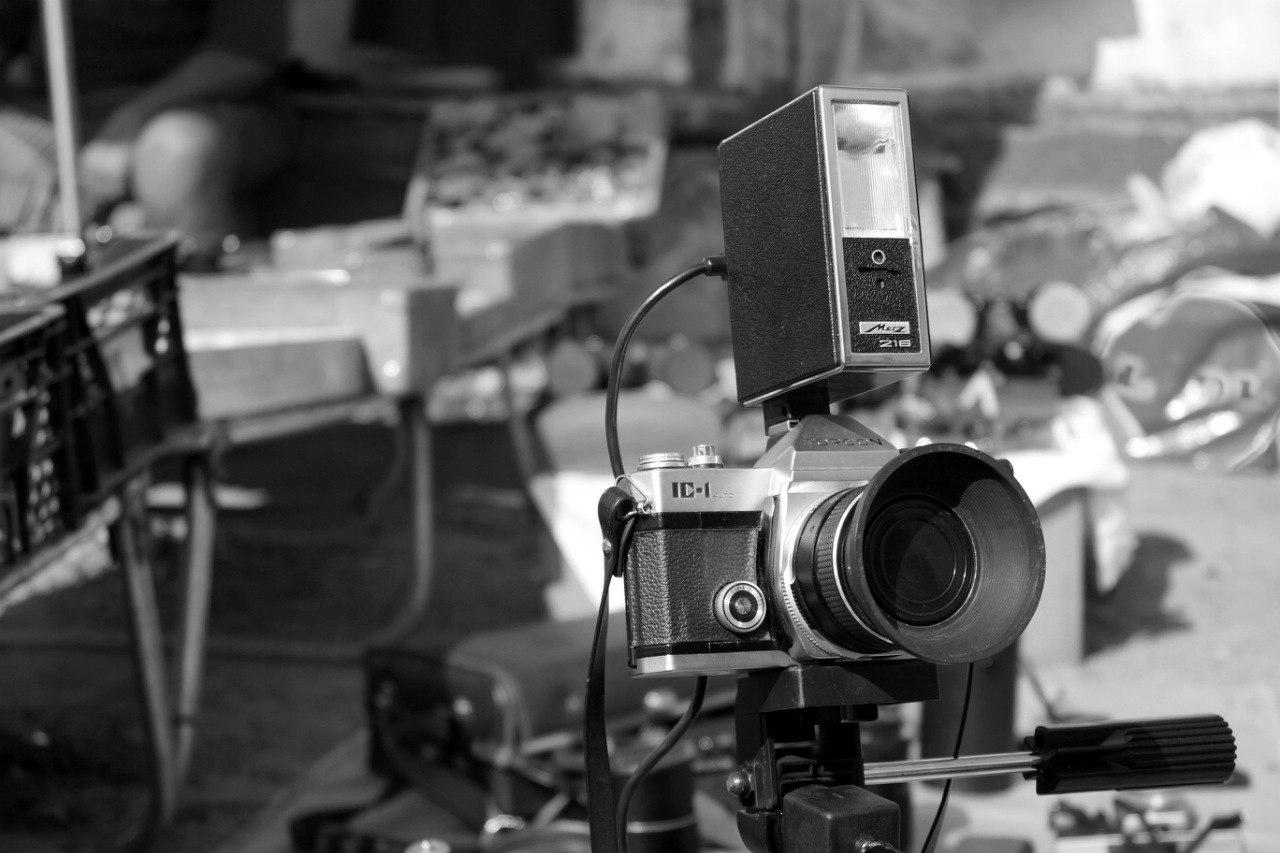 пленочный фотоаппарат на штативе со вспышкой