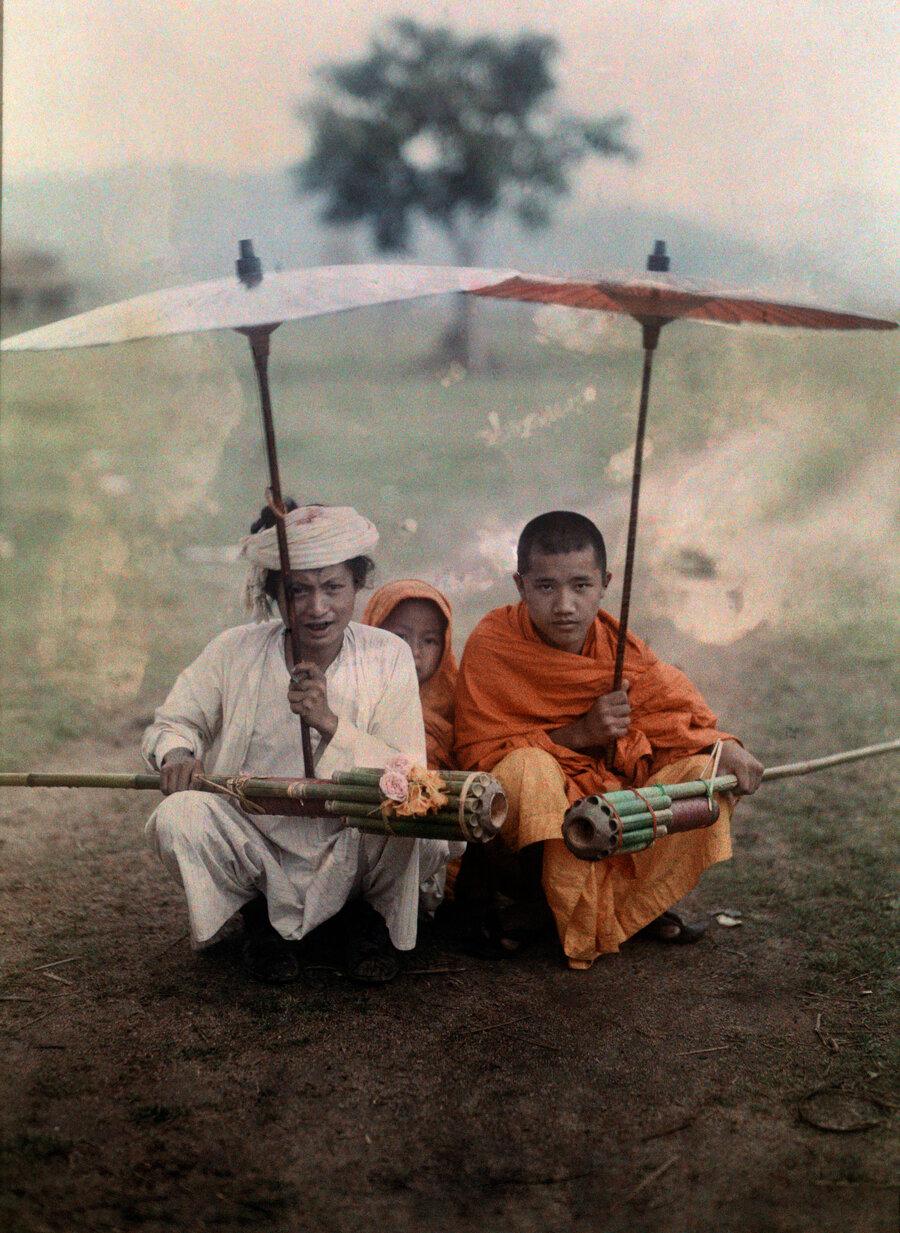 1930. Индия.  Мужчина и двое священников сбамбуковыми ракетами под дождем