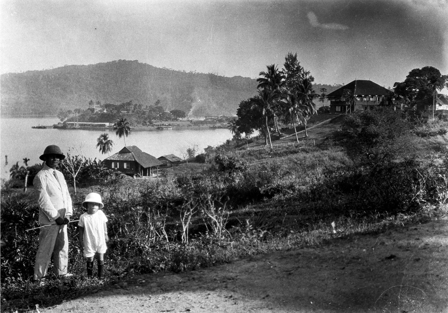 1132. Мужчина и ребенок в тропических костюмах. Порт-Блэр на заднем плане