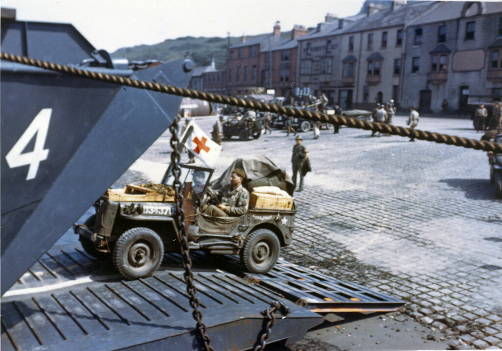Jeeps being driven into the open doors of an L.C.T. at a port in Britain in preparation for D-Day.