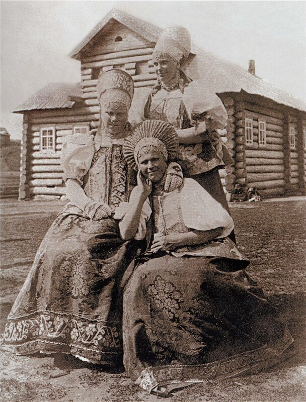 Молодая женщина в кокошнике-сборнике и девушки в повязках на празднике в...