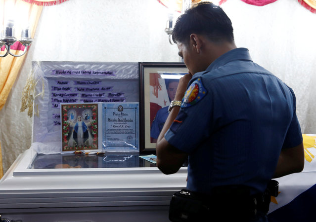 A policeman pays his respects to fellow officer Rancel Cruz, whom police investigators said was shot