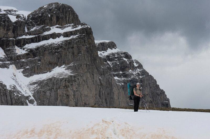 турист с рюкзаком, снег и гора Астрака в Греции