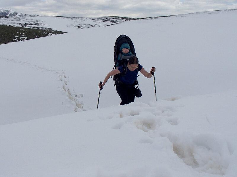 мама в горном походе несет ребенка по снегу в рюкзаке Deuter