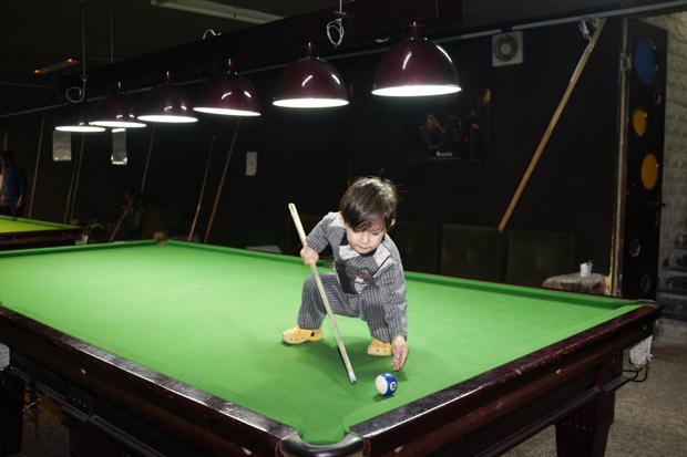 Ребенок играет на бильярдном столе в подвале отеля в Дизине. Горы Альборз, 31 декабря 2014 года. «Ес