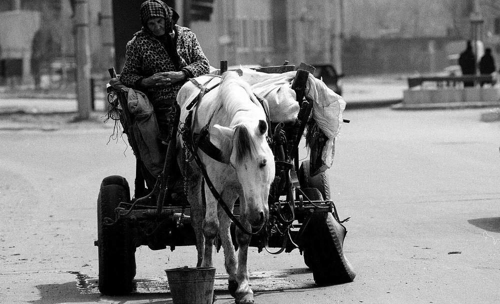 Женщина ждет, пока кто-нибудь поможет ей заменить колесо на телеге. В некоторых регионах Румынии все