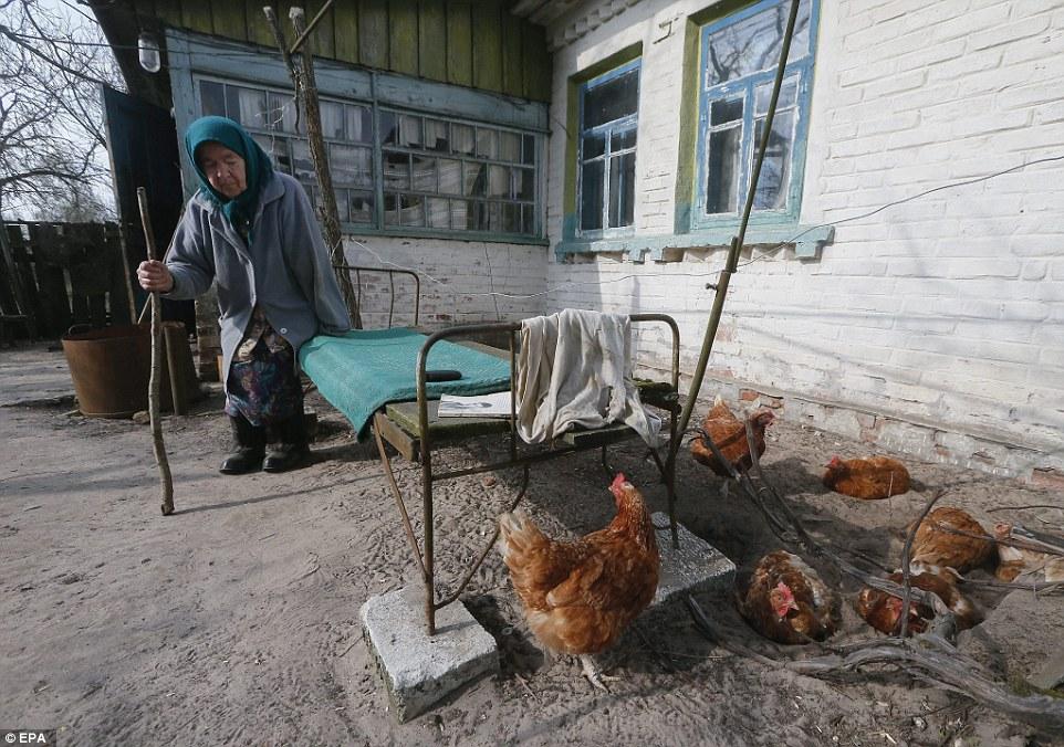 Мария Семенюк, жительница Чернобыльской зоны, сидит возле своего дома с домашними курами.