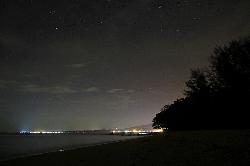 Ночь, небо, звёзды, огни отелей и домов на далеком мысу, след от китайского бумажного фонарика. Пляж White Sands Beach в Khao Lak, Таиланд
