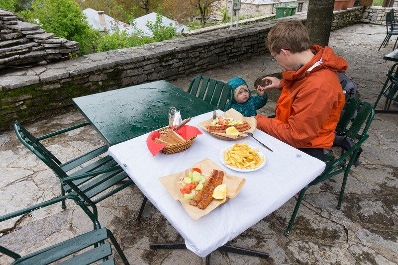 обед в греческой таверне жареными колбасками и картошкой