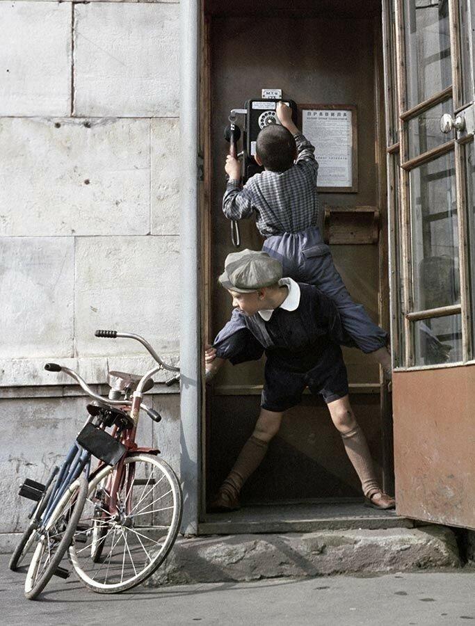 Мальчик залез на спину товарищу, чтобы позвонить по телефону-автомату