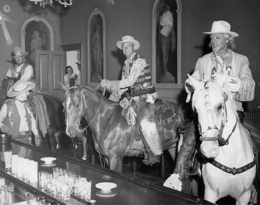 Riders in Teller House Bar. Members of the Roundup Riders of the Rockies pose on horseback inside the Teller House Bar in Central City (Gilpin County), Colorado. Burr Betts is dressed to look like Buffalo Bill Cody, and wears long wavy hair, a goatee, a fringed leather coat and gauntlets decorated with the 3R logo.1958