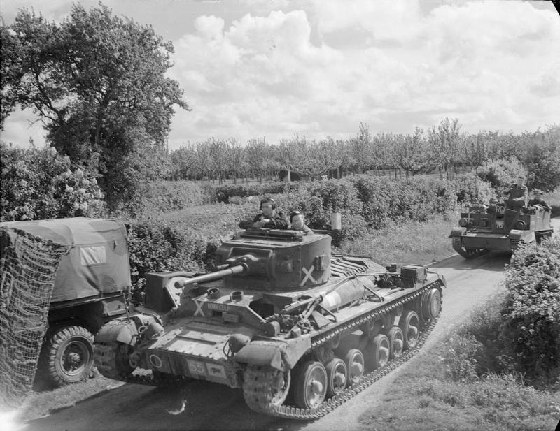 "Valentine tank of 11th Armoured Division, marked with crosses to indicate an ""enemy"" vehicle, followed by a universal carrier, during exercises in Kent, 30 May 1942."
