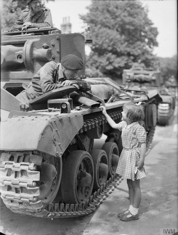 Trooper Bill Blackett, the driver of a Valentine tank of 29th Armoured Brigade, 11th Armoured Division, chats to Pat Brooker, aged 5, during a halt in the village of Rottingdean in Sussex, 25 June 1942.