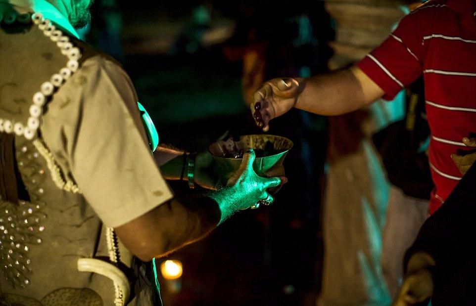 Обряд жертвоприношения: кровь жертвенных цыплят и коз собирают в бронзовый сосуд, а затем вылива