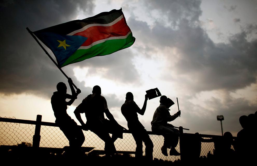 32. Жители Южного Судана с флагами радуются дню независимости во время первого матча по футболу в Дж