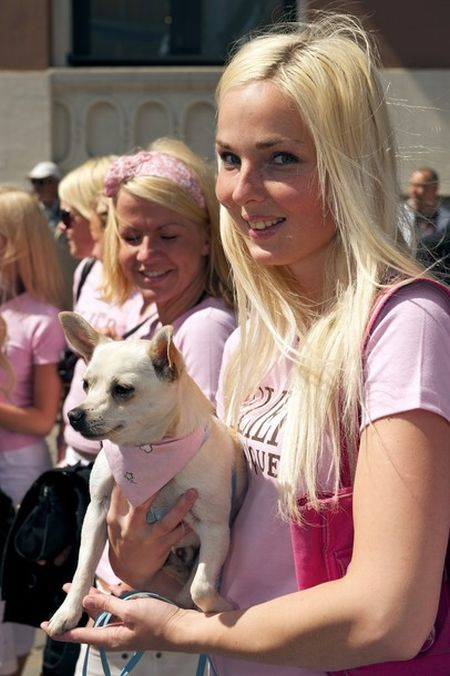 A Blonde poses with her dog as they para