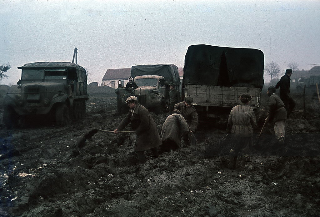 German army vehicles on muddy terrain in the Ukraine; civilians at roadworks - no further details - spring 1942 - Photographer Wolff & Tritschler.jpg