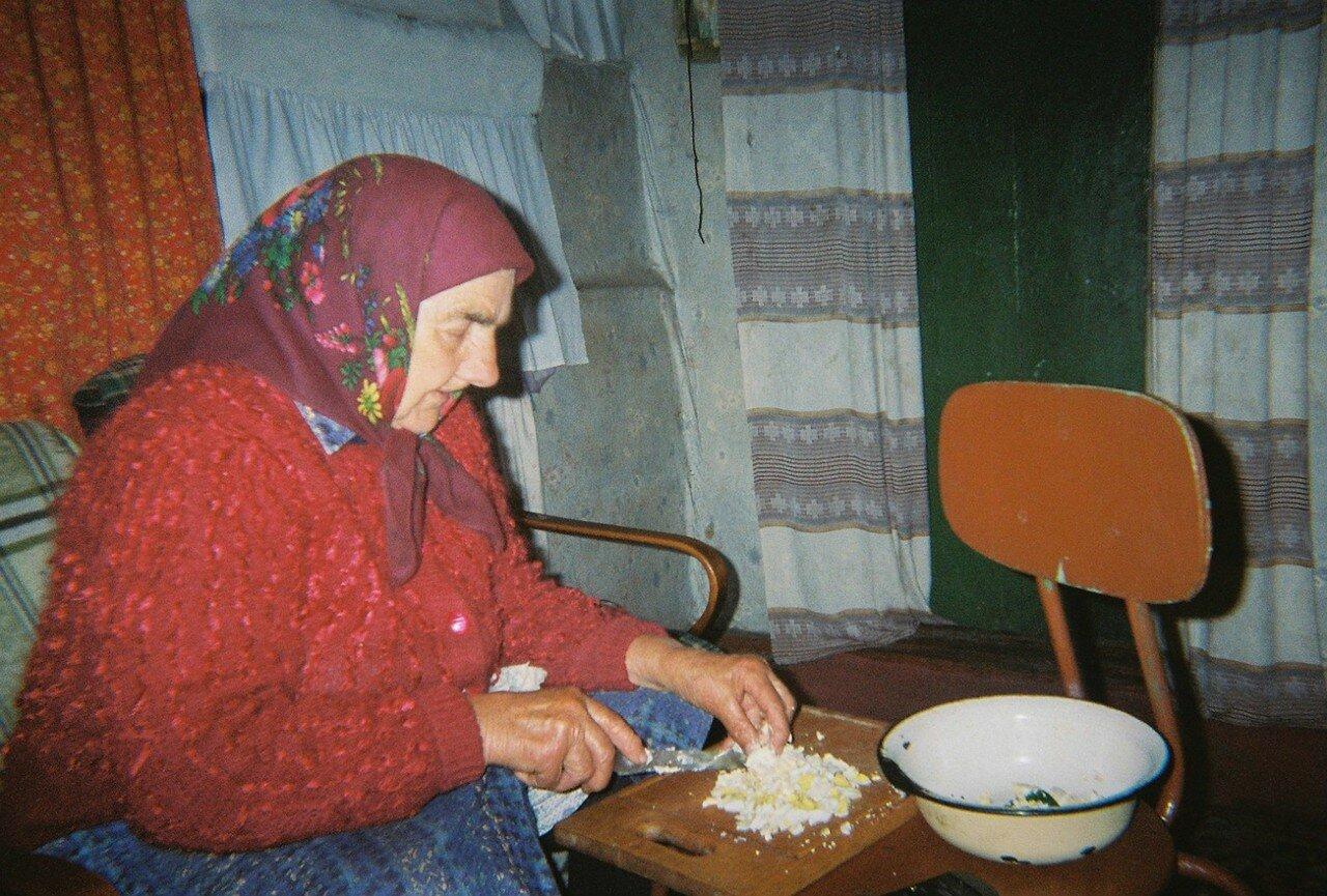 Пожилая женщина готовит пищу в своем доме недалеко от Чернобыля