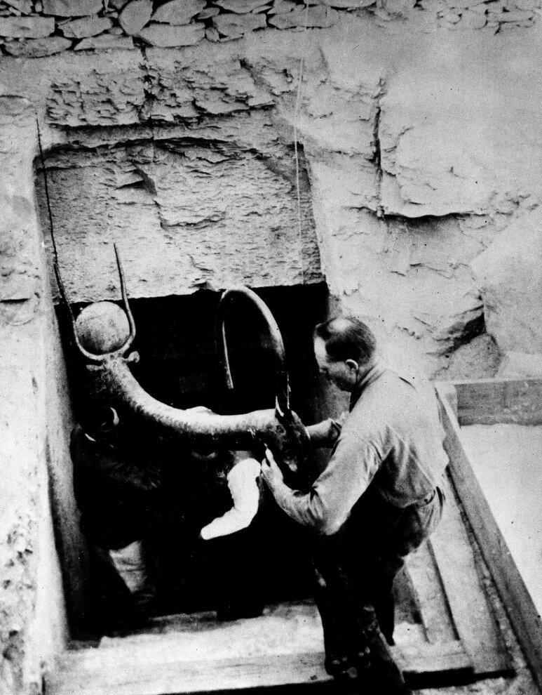Археологи достают предмет из гробницы фараона Тутанхамона в долине фараонов в Луксоре, Египет, 1923