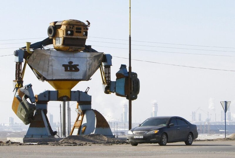 A car passes by a giant transformer, made of discarded old cars and scrap metal, outside the town of Yuzhny, some 40 km (25 miles) south of the Black Sea port of Odessa