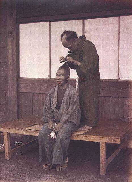 Мужской парикмахер делает прическу