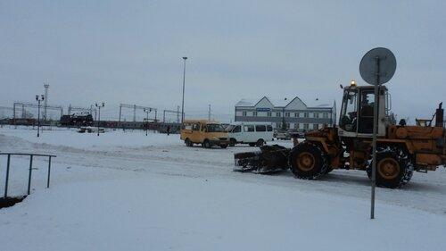 расчищают от снега площадку у автостановки