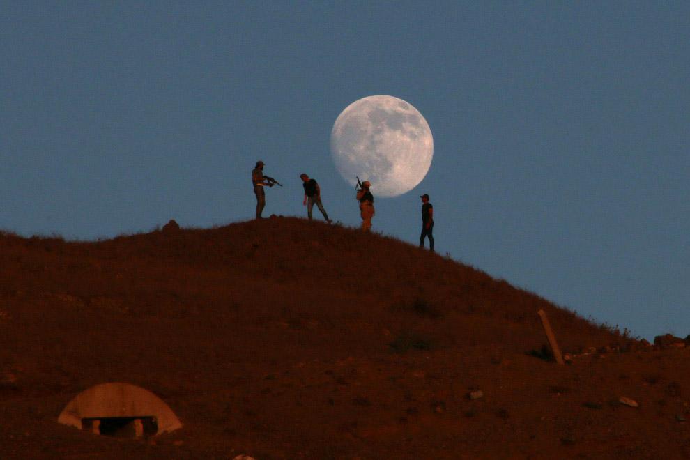 8. Полная Луна выглядывает в трущобах Рио-де-Жанейро, где проходит Олимпиада, 17 августа 2016.