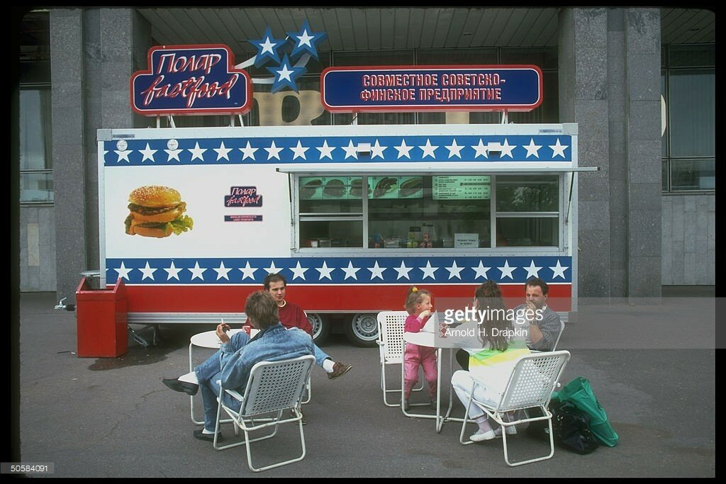 1989 Polar fast food kiosk, joint Finnish-Russian venture, w. patrons dining alfresco at tables set up in front of gaily painted stand.jpg