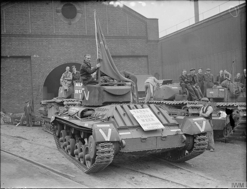 "Factory workers ride on Valentine tanks as they leave a factory in Smethwick. The notice on the tanks reads ""Tanks for Russia Week. Every Second Counts!"", ""From Smethwick to Smolensk""."