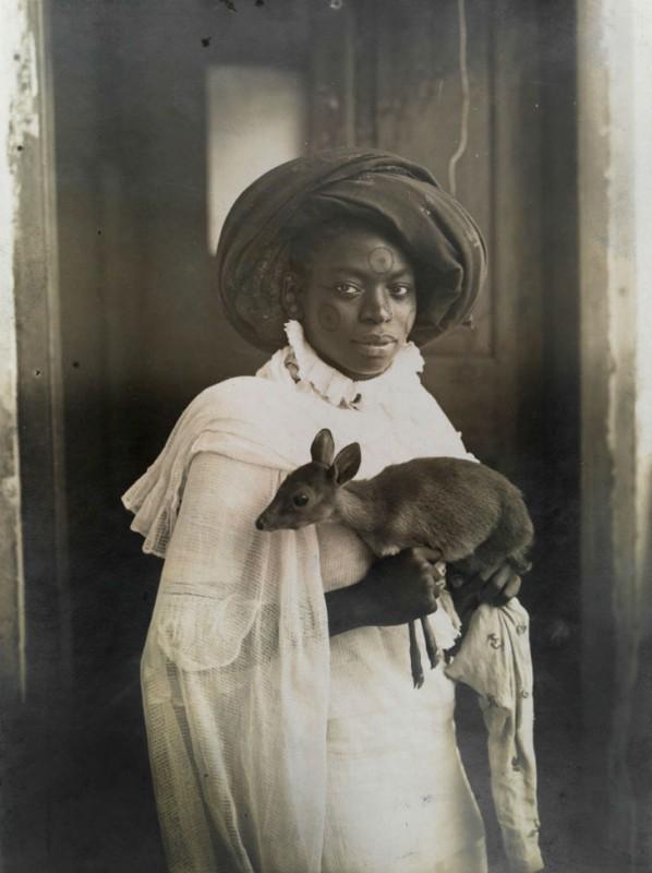 Молодая кенийская женщина держит на руках своего домашнего олененка, Момбаса, 1909 год.