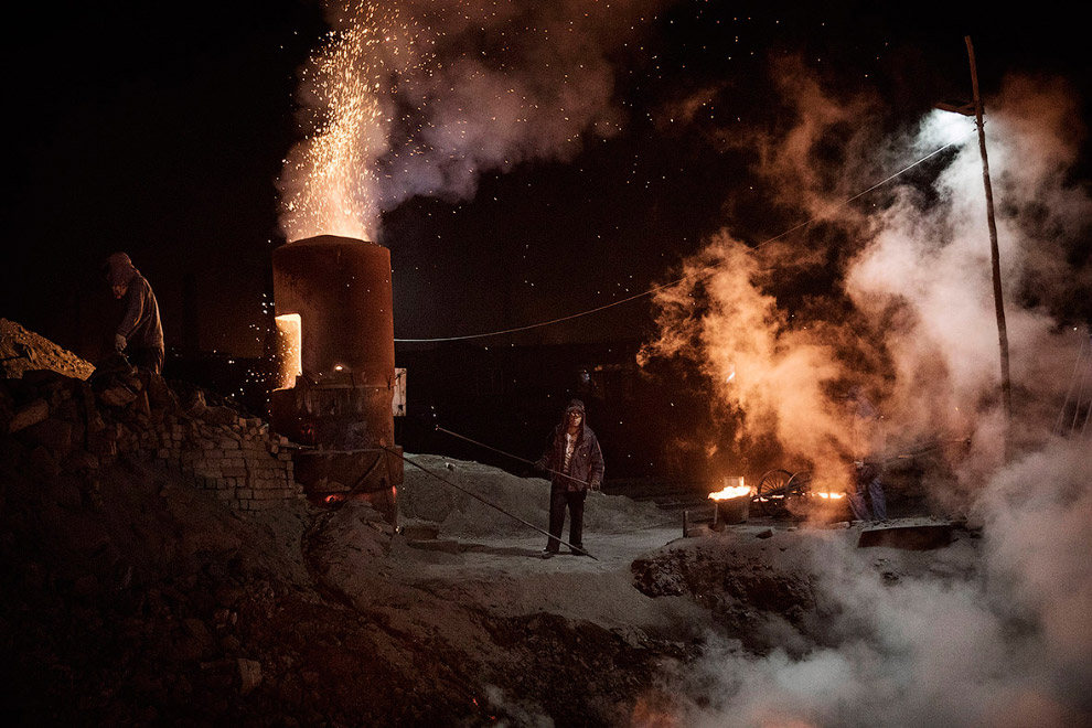 6. Пока в печи горит уголь, из нее вытекает расплавленный метал. (Фото Kevin Frayer):