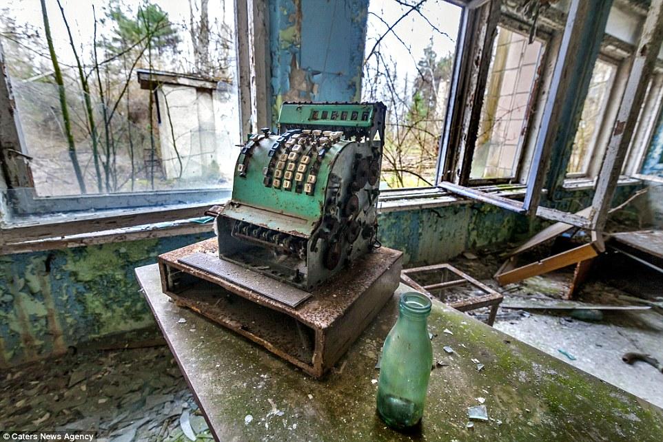 Сохранившиеся кассовый аппарат и стеклянная бутылка в заброшенной школьной столовой, где плесень рас