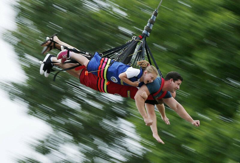 Восьмилетняя Лилли Кэрон с отцом на аттракционе «Катапульта» в парке развлечений Seacoast Adventure в Уиндеме, штат Мэн, 4 июля 2016 года. (Robert F. Bukaty / AP)