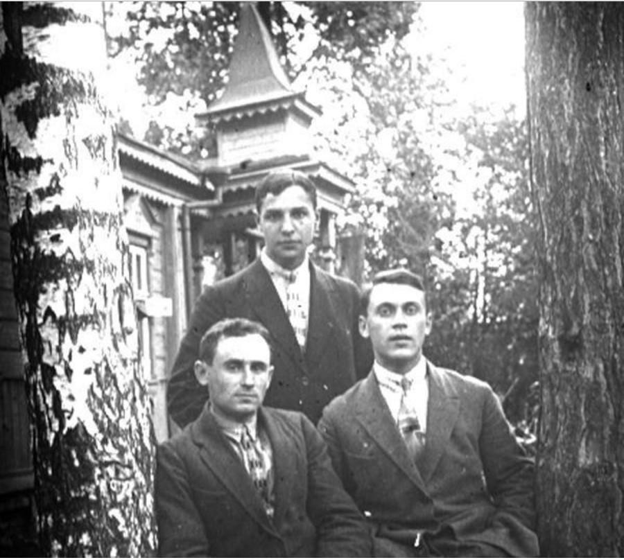 Трое мужчин в палисаднике перед домом