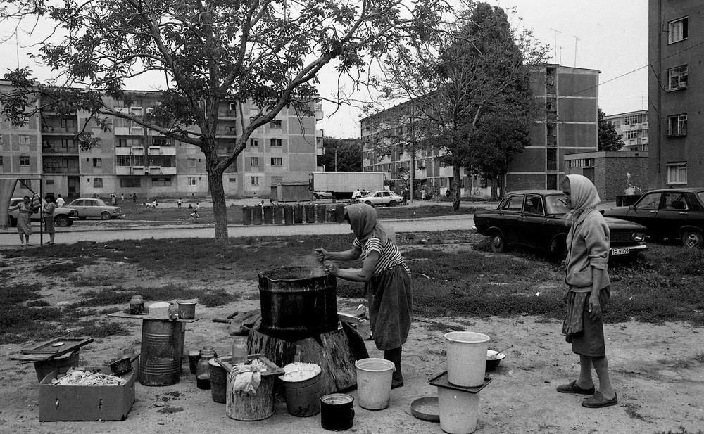 Женщина варит мыло из животного жира во дворе.