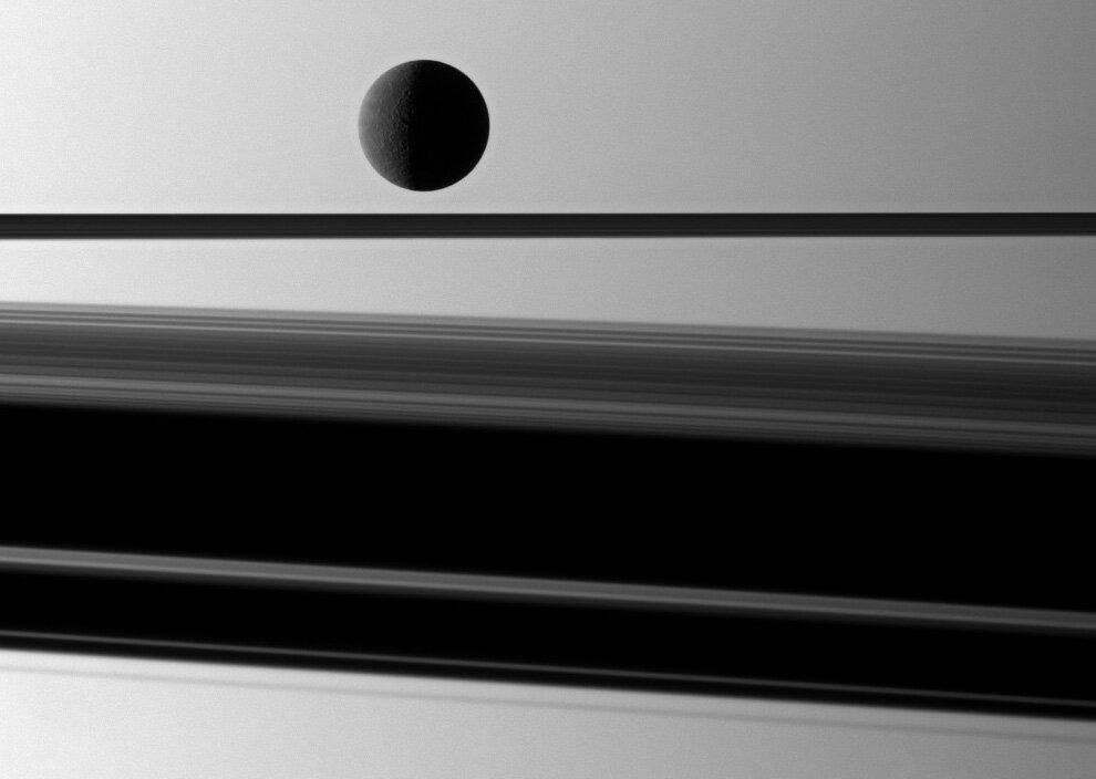 Спутник Сатурна Рея (1528 км) слегка подсвечивается перед планетой